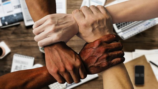 four arms and hands of different skin tones interlock