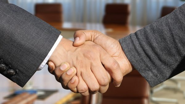 Two people shake hands to signify partnership