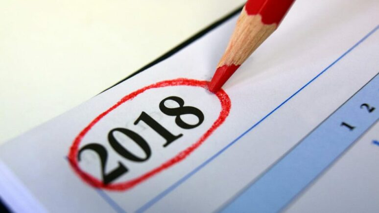 Red pencil sitting on a calendar with the year 2018 circled in red