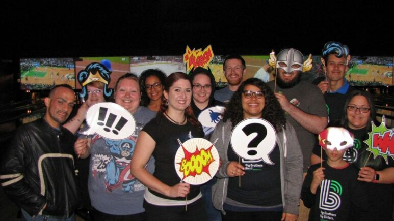 InCheck employees pose with superhero props in a bowling alley
