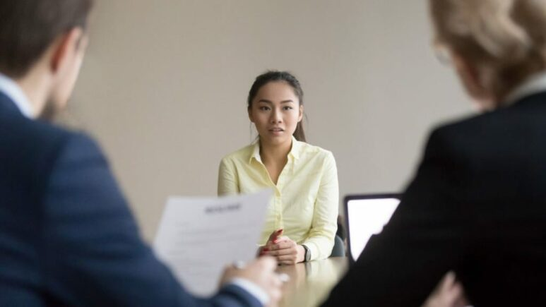 job candidate sitting across the table from two hiring managers