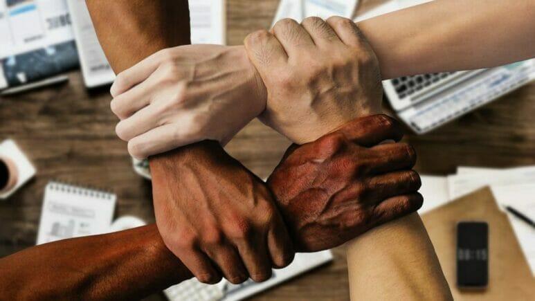 four hands of different ethnicities interlocked