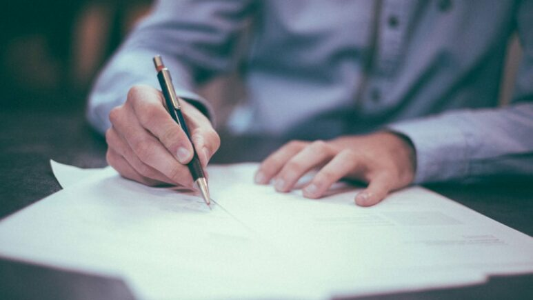 man sitting at table writing and filling out paperwork