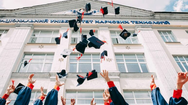 school graduates standing in front of school throwing their graduation caps in the air