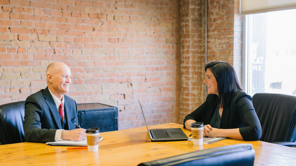 Two professionals sitting at a table discussing the PBSA