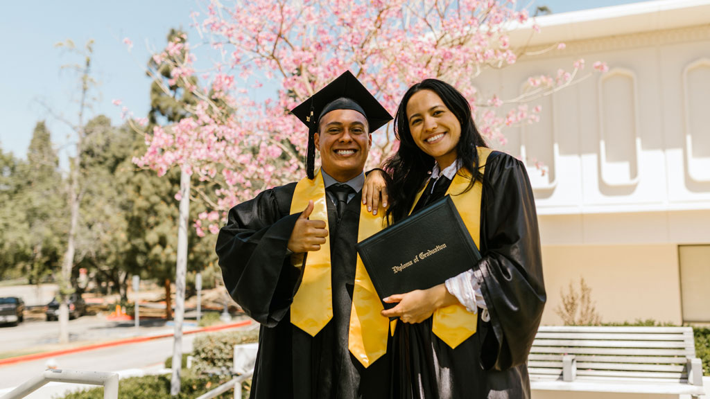 two students standing in cap and gown displaying their diploma